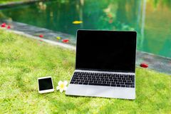 Laptop computer and mobile phone in grass by the pool. Laptop computer and mobile phone in grass by the tropical pool stock photos