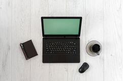 Laptop, computer mouse, cup of coffee and notebook on a wooden table. Stock Images
