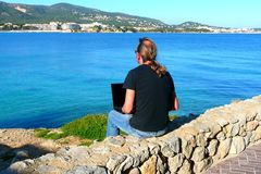 Laptop computer near the beach. A Man working on a laptop computer by the sea Royalty Free Stock Photos