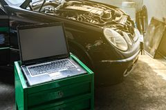 Laptop or computer notebook interfaced with car for repair during work investigate cause of problem program and electric system. Check or working on automobile stock photo