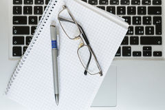 Laptop computer with notepad, pen, glasses and keyboard Royalty Free Stock Image