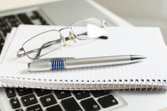Laptop computer with notepad, pen, glasses and keyboard Royalty Free Stock Photography