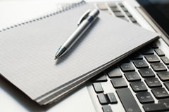 Laptop computer with notepad, pen on ivory table Royalty Free Stock Photo