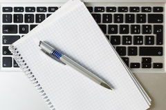 Laptop computer with notepad, pen and keyboard Stock Photography