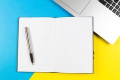 Laptop-Computer, offenes Papiernotizbuch und Stift auf blauem und gelbem Farbhintergrund Stockbild