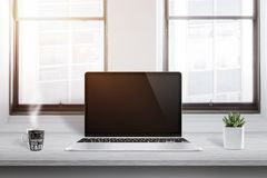 Laptop computer on office desk with cup of coffee and plant beside Royalty Free Stock Photography
