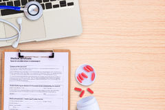 Laptop computer and pill with blue stethoscope on wooden desk. Stock Images