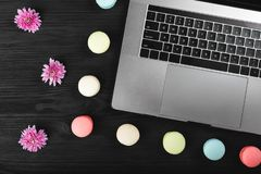 Laptop computer, pink flowers and macarons on a wooden desk, top view copy space stock photo