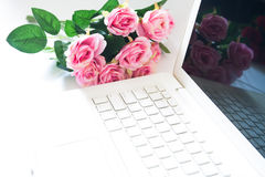 Laptop computer with pink rose bouquet in background. Technology Royalty Free Stock Photos
