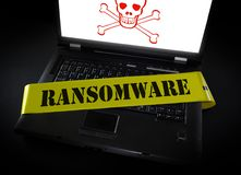 Ramsomware computer crime scene tape. Laptop computer with Ransomware crime scene tape across it and skull and crossbones royalty free stock image