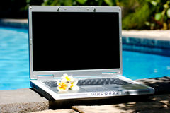 Laptop computer and resort poo Royalty Free Stock Photos