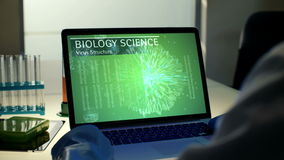 Laptop computer screen with animated interface of scientific program analyzing pathogen virus structure. Scientist in stock video footage