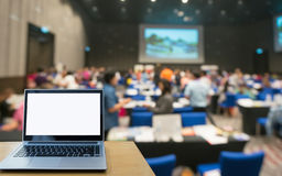 Laptop computer seminar room in attendee background. Blank screen laptop computer on the Abstract blurred photo of conference hall or seminar room with attendee Royalty Free Stock Photos