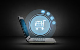 Laptop computer with shopping cart icon projection Stock Photography