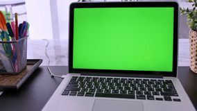 Laptop Computer Showing Green Chroma Key Screen Stands on a Desk in the Living Room. In the Background Cozy Living Room. Dolly Zoo stock video