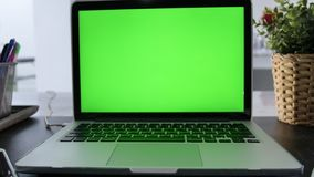 Laptop Computer Showing Green Chroma Key Screen Stands on a Desk in the Living Room. In the Background Cozy Living Room. Dolly Sho stock footage