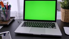 Laptop Computer Showing Green Chroma Key Screen Stands on a Desk in the Living Room. In the Background Cozy Living Room. Tilt down stock video footage