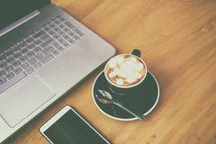 Laptop computer with smarth phone on wooden desk in business roo. M. A cup of coffee in coffee break time Film grain effect Royalty Free Stock Photos