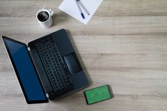 Laptop computer with smartphone, hot coffee cup, pens and paper on wooden desk Stock Images