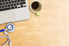 Laptop computer and stethoscope. With cup of coffee on office desk background. top view with copy space. Health concept Stock Images