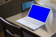 Laptop Computer On Table. Apple Powerbook G4 notebook computer with blue screen sitting on stainless steel kitchen table complete with clipping path around the stock image