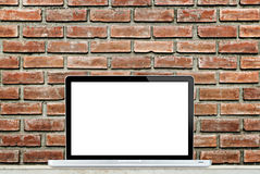 Laptop computer on table with brick wall background Royalty Free Stock Images