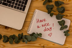 Laptop computer, text Have a nice day and eucalyptus branches on Stock Image