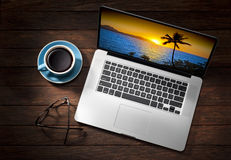 Laptop Computer Travel Business Holiday Vacation. A still life of a laptop computer from above on a wood background with a cup of coffee, glasses and a tropical royalty free stock photos