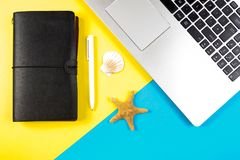 Laptop computer, travel notebook and seashells and starfish over blue and yellow background. Vacation, travel planning concept. Laptop computer, travel notebook Royalty Free Stock Photography