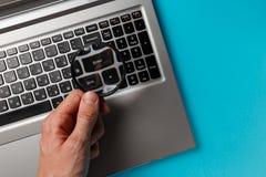 Laptop-Computer und die Hand des Mannes mit Lupe auf blauem Hintergrund, Konzept der Suche lizenzfreie stockfotografie