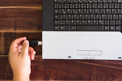 Laptop-Computer und Hand mit USB-Blitz fahren Selektiver Fokus Stockfotografie