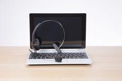 Laptop-Computer und Kopfhörer auf einem Schreibtisch Lizenzfreies Stockfoto