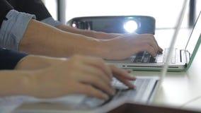 Laptop-Computer und zwei Kollegen, die Daten besprechen stock video footage