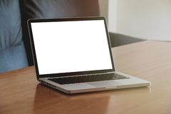 Laptop computer with white blank screen. On a wooden table stock image
