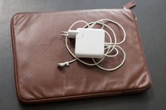 Laptop computer white charger brown leather case Stock Images