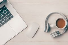 Laptop computer on white table with headphone and coffee cup. Vi Stock Image
