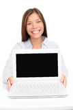 Laptop computer - woman showing screen smiling. Happy. Focus on pc display for copy space text or design. Beautiful happy multicultural Asian Caucasian female Royalty Free Stock Photo