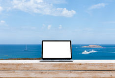 Laptop computer on wood table with sea background Royalty Free Stock Photos
