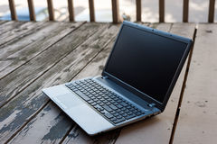 Laptop computer on wooden floor with blank screen Stock Photo
