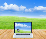 Laptop computer on wooden floor with green fields and blue sky b Royalty Free Stock Photography