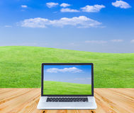 Laptop computer on wooden floor with green fields and blue sky b. Ackground Stock Photos