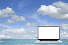 Laptop computer on wooden floor with sky background. Royalty Free Stock Photography