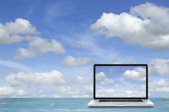 Laptop computer on wooden floor with sky background. stock images