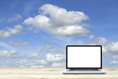 Laptop computer on wooden floor with sky background. White Royalty Free Stock Image
