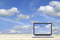 Laptop computer on wooden floor with sky background. White Royalty Free Stock Images