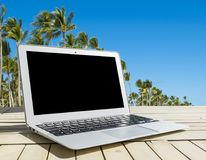 Laptop computer on wooden table. Front palm view. Tropical island background. Open blank laptop computer empty space. Front view Royalty Free Stock Photo