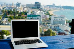 Laptop computer on wooden table with modern city view.  royalty free stock photography
