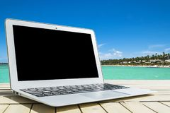 Laptop computer on wooden table. Top ocean view. Tropical island background. Open blank laptop computer empty space. Front view Royalty Free Stock Images