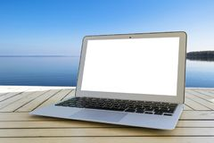 Laptop computer on wooden table. Top ocean view. Tropical island background. Open blank laptop computer empty space. Front view. With copy space. Isolated white Royalty Free Stock Photos