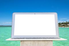 Laptop computer on wooden table. Top ocean view. Tropical island background. Open blank laptop computer empty space. Front view. With copy space. Isolated white Stock Photo